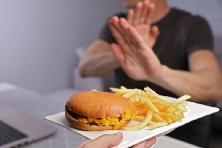 Man refusing burger to prevent cholesterol
