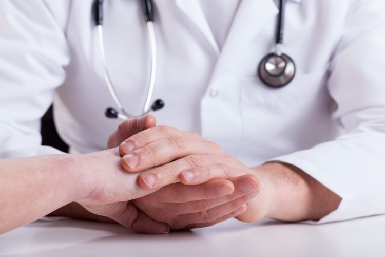 Doctor With Sthethoscope Holding Woman's Hand Talking About Hypertension Diagnosis